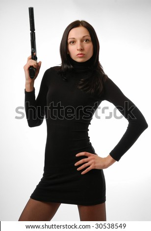 Imperturbable woman taking up handgun. Black short dress accentuates slim figure. Left hand put on hip. - stock photo