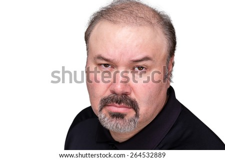 Implacable overbearing middle-aged man looking at the camera with a stern expression and baleful glare, head and shoulders isolated on white