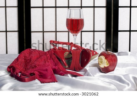 Implied sex with a bite taken from the forbidden fruit.  Red brassiere, high heel shoes, wine, and an apple.  On white silk. - stock photo
