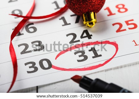Important New Year's Eve date which is led round in a calendar. A note for a meeting, closeup