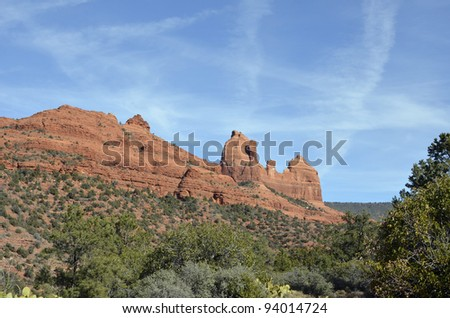 Imposing and majestic red rock cliffs and monuments contrast with deep green vegetation in scenic Sedona, where mystery is palpable and the natural beauty, overwhelming. - stock photo