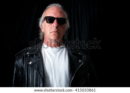 Imposing image of older biker against black backdrop looking down at viewer from behind vintage sunglasses. wearing vintage black leather jacket and white t shirt.