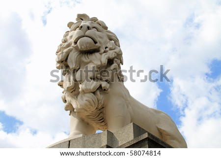 Imposing lion statue guarding the south bank of the Thames River near the London Eye ferris wheel attraction in London - stock photo