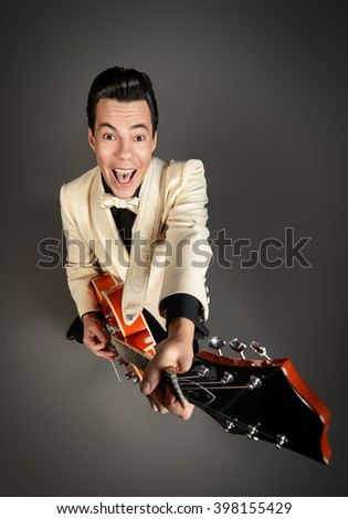 Imposing male musician  plays and sing in the style of the sixties. Rock'n'roll, jazz man. Beat generation. - stock photo