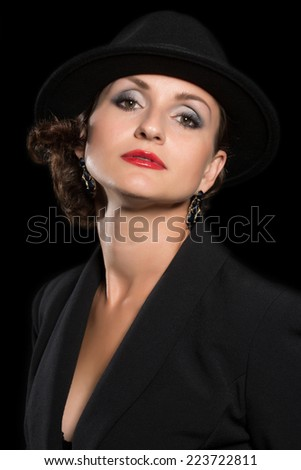 Imposing woman in a hat on a dark background. Woman 36 years old.