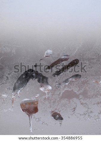 Impression of a human hand on icy glass       - stock photo