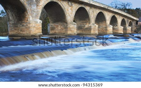 Impressive ancient Bridge found in Hexham, England over stunning Blue atmospheric soft Waterfall - stock photo