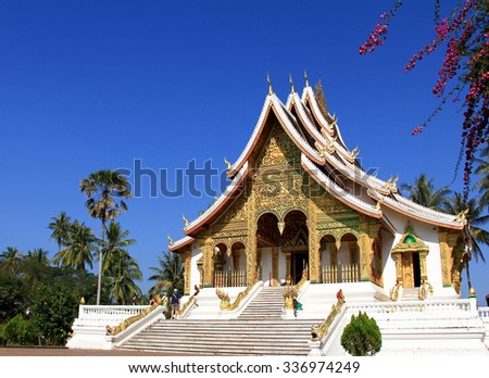 Impressive buddhist temple during a clear sunny blue sky in world heritage town of Luang Prabang - stock photo