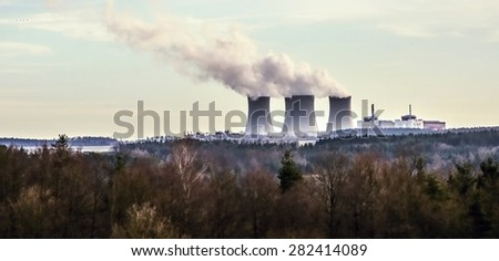 Impressive cooling towers of nuclear power plant Temelin, behind nice winter forest in lovely landscape