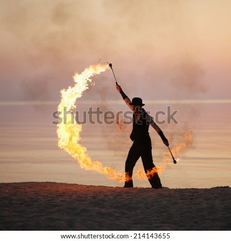 Impressive fire show on the beach at summer - stock photo