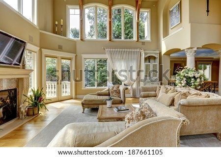 Impressive high ceiling living room with tv, fireplace and antique furniture - stock photo