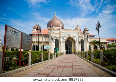 impressive mosque architecture with front bricks walk way blue sky white clouds - stock photo