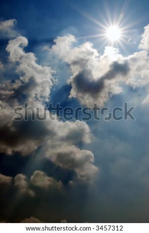 impressive threatening cloudy sky with sun and sunrays - stock photo