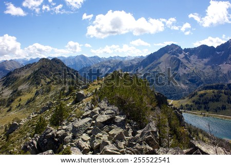 Impressive view of a rocky steep ridge in the mountain pyrenees above a blue lake, a mountain range in the background and a blue sky with some white clouds - stock photo