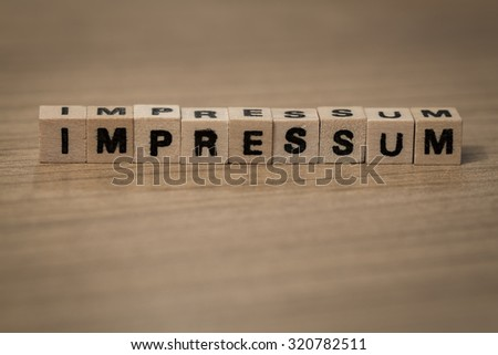 impressum (german imprint) written in wooden cubes on a desk - stock photo