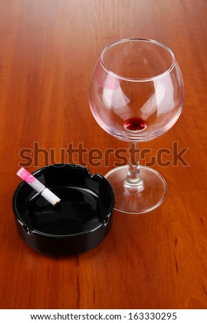 Imprint lipstick on glass and cigarette on wooden table close-up