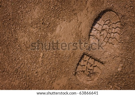 Imprint of the shoe on mud with copy space - stock photo