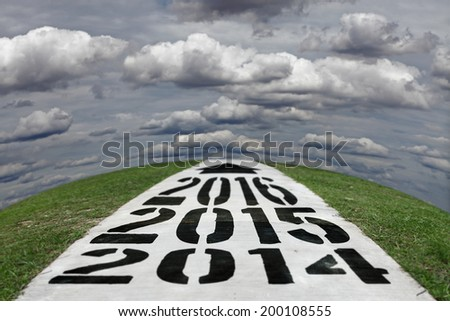 Imprint of the timeline for Year 2014, 2015 and 2016 on a concrete road vanishing across the horizon of a grassy hill into a cloudy sky, for the concept of countdown to new year 2015. - stock photo