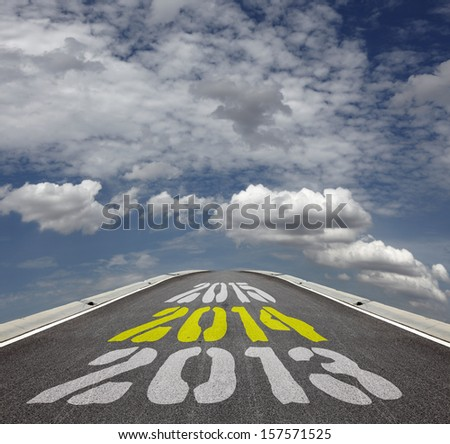 Imprint of the timeline for Year 2013, 2014 and 2015 on an asphalt road vanishing across the horizon of a blue cloudy, for the concept of countdown to new year 2014. - stock photo