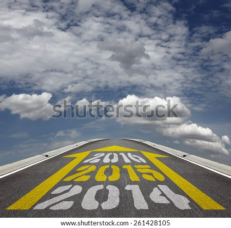 Imprint of Year 2014, 2015 and 2016 timeline in a yellow arrow on an tarmac road vanishing into the horizon of a blue cloudy sky. - stock photo