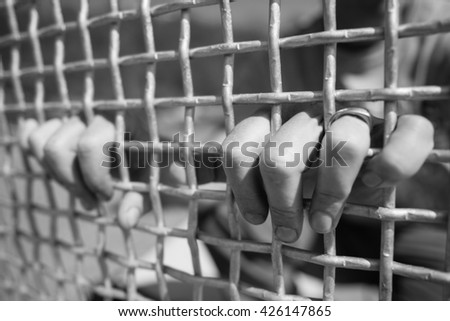 Imprisoned man places fingers through metal fence and holds - stock photo
