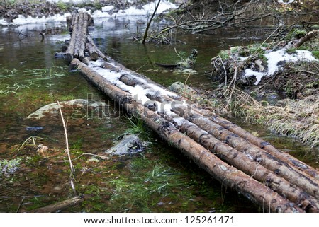 Improvised bridge from logs in forest covered in snow