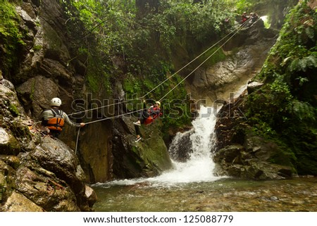 IMPROVISED ZIP LINE DURING A CANYONING TOUR IN ECUADORIAN RAINFOREST  - stock photo