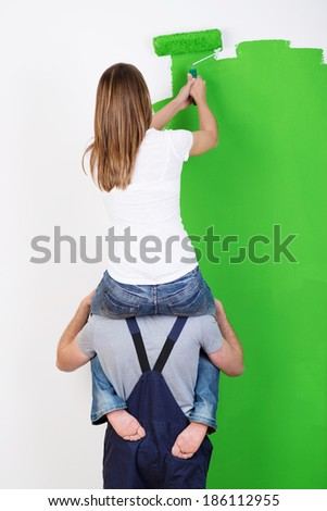 Improvising when you do not have a ladder as a young woman sits on her husbands shoulders to gain extra height when painting the wall at their home - stock photo