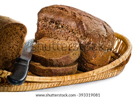 In a basket two small loaves of rye bread, one of the two pieces cut with a knife