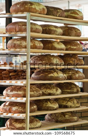 In a bread bakery, food factory. Many freshly baked breads which are put on the shelf for cooling down. - stock photo