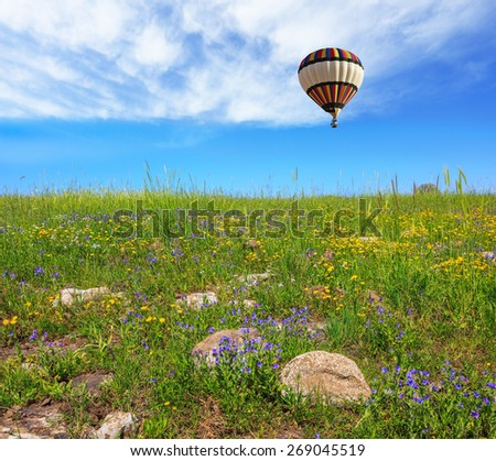 In a clear sky flying big colorful balloon. Flowering Golan Heights in a beautiful sunny day - stock photo