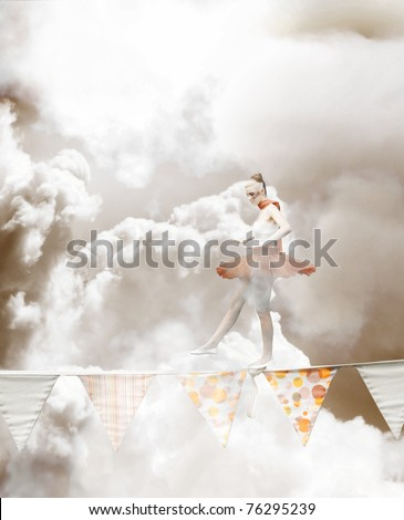 In A Cloudy Portrait Of Determination And Skill At Great Heights A Ballerina In Tutu Walks Along A Tight Rope In A Show Of Stability Acrobatics And Balance - stock photo