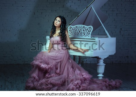 In a dark room girl sitting at a white grand piano. - stock photo