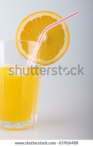 in a glass of orange juice with a straw and a slice of orange and ice