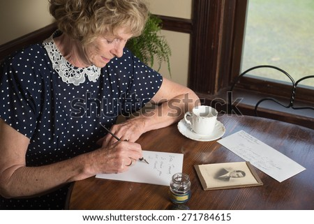 In a historical scene from the 1930�¢??s or 1940�¢??s, an attractive elderly woman writes a letter as she sits at a table by a window. - stock photo