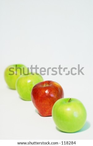 In a line of green apples, someone just had to be red. - stock photo