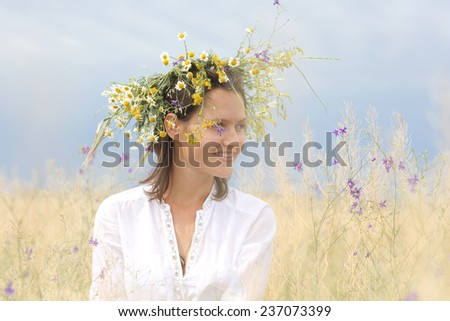 in a lush field girl with a wreath of flowers on her head - stock photo