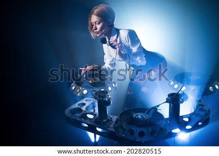 In a nightclub, under the light of the lamps, girl playing on vinyl