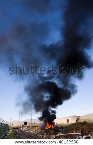 In a region sub-urban town of Adrano in Sicily was created an illegal landfill site where they have destroyed by fire of awnings of car and is lifted a long column of black smoke - stock photo
