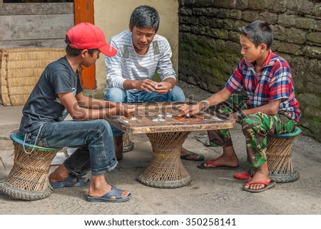 In a small village on Around Annapurna trek trail, Nepal-October 17, 2008: Two youngsters play some Nepali version of table billiard game using their fingers to shoot a puck into the opponent's puck