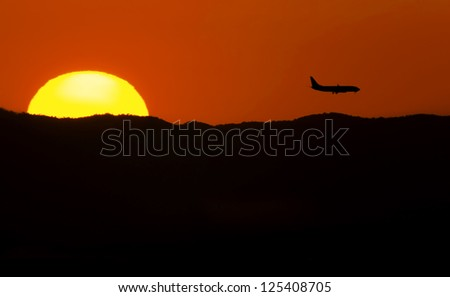 In a summer afternoon a plane flies in final approach - stock photo