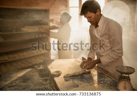 In a traditional bakery, bakers prepare the dough for the bread. The morning sun comes in through the window