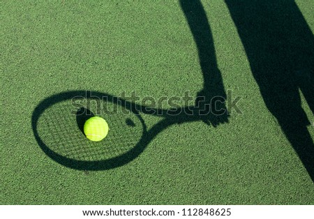in action on a tennis court (conceptual image with a tennis ball lying on the court and the shadow of the player positioned in a way he seems to be playing it) - stock photo