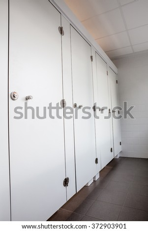 In an public building are womans toilets with white doors