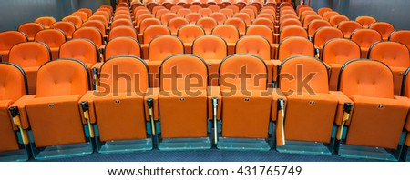 in an small theater there are orange seats in a row - stock photo