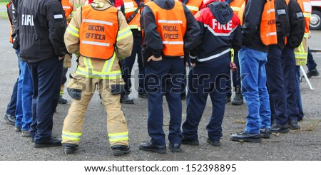In any urban area the fire departments and emergency response teams will conduct disaster preparedness drills. This group of team members gathers around to discuss options. - stock photo