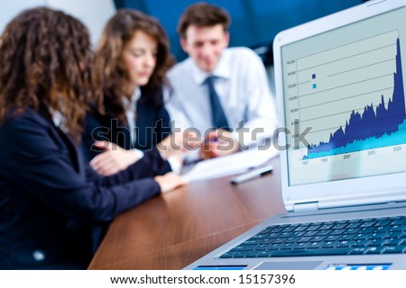 In background happy young business people having meeting at office. In front focus placed on graph shiwing progress on laptop screen. - stock photo