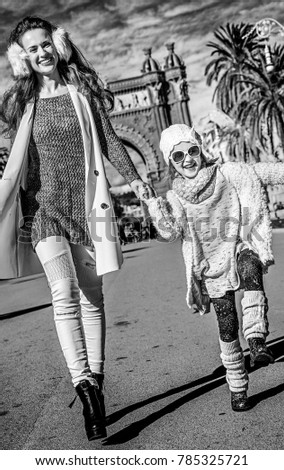 in Barcelona for a perfect winter. happy trendy mother and daughter near Arc de Triomf in Barcelona, Spain walking