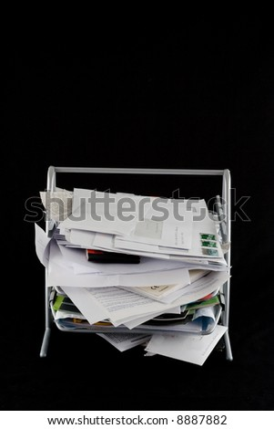 In-basket overflowing with papers,mail and other documents. Isolated on black background. - stock photo