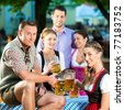 In Beer garden - friends in Lederhosen drinking a fresh beer in Bavaria, Germany - stock photo